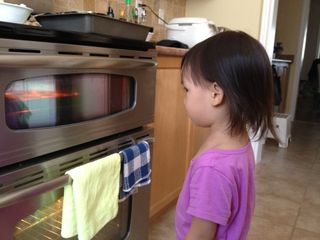 My daughter watching cupcakes bake in oven