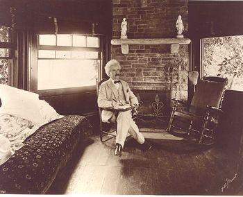 Mark Twain seated writing