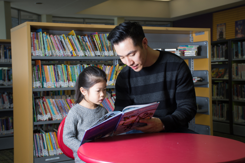 adult reading to a child in the library