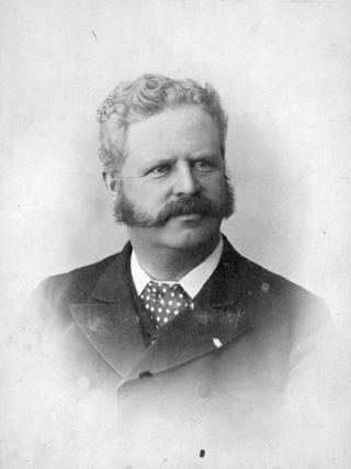 Black and white portrait of a man with a mustache in a buttoned up jacket.
