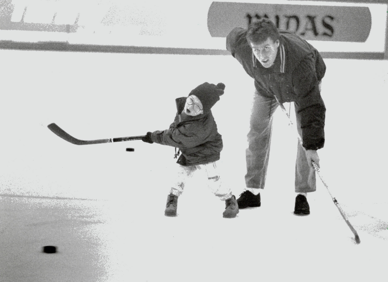 Dave Hannan playing hockey with his three year old son