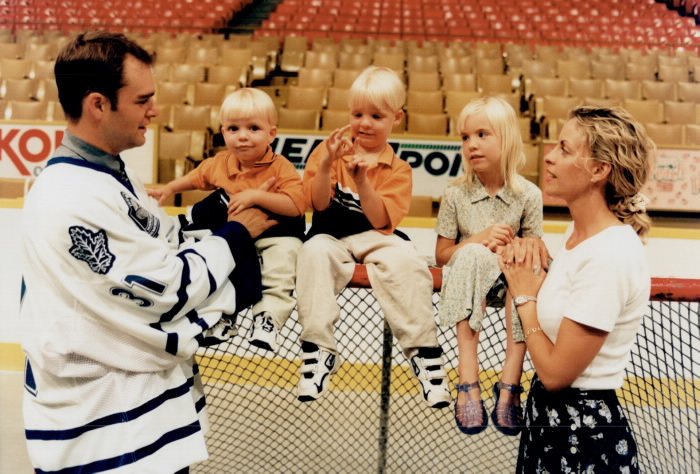 Hockey player Curtis Joseph  his wife and three children sitting on a hockey goal