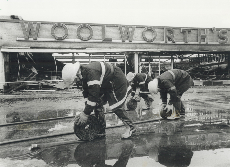 Three fire fighters rolling up hoses in front of of a burnt Woolworth's building