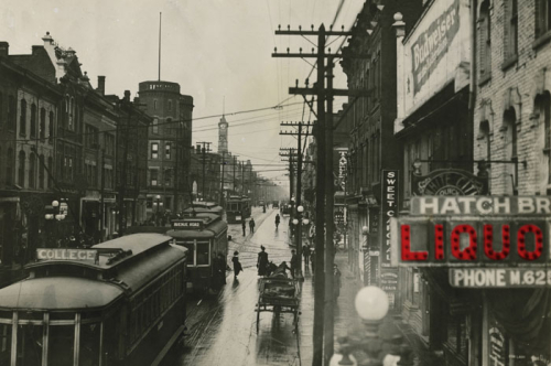 Black and white photograph of Yonge St., Queen to College Sts., looking north from north of Granby St. A sign for Hatch Bros. Liquor has been digitally coloured red.