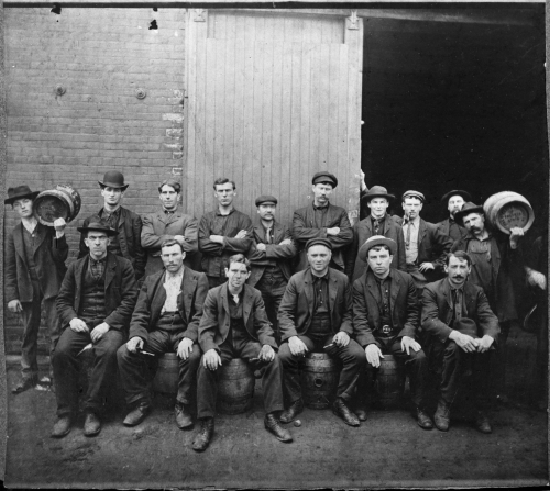 Black and white portrait of 16 men. Half are seated. Two hold barrels of beer.