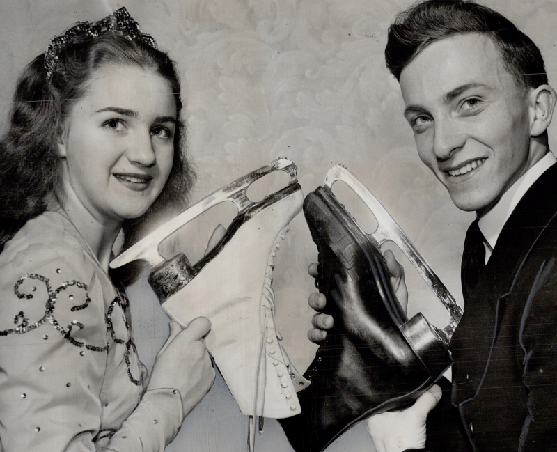 Two figure skaters holding up their skates to pose for a photo