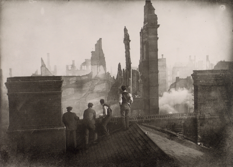 Four men on a roof looking out at ruins from a fire