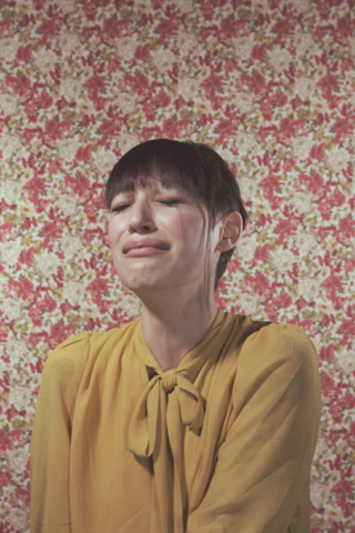 Young woman crying against floral background