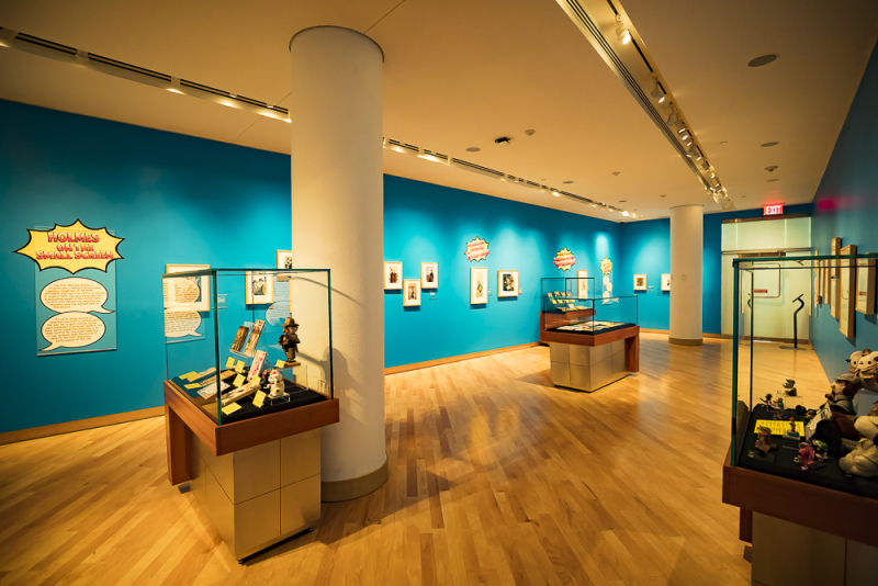 Interior of gallery with glass display cases displaying books and collectibles. Pop-art style graphics appear on panels on the walls.