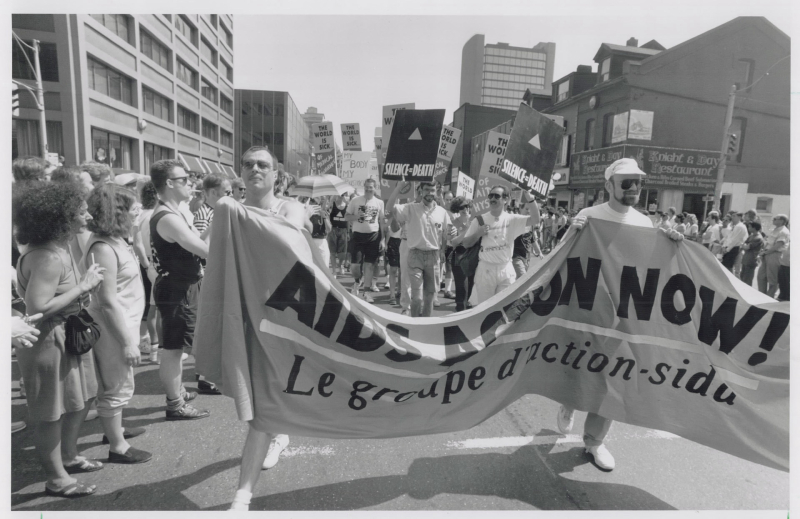 Toronto Star photo - 1989 Gay Pride Day celebrants line Yonge St. yesterday to support those who marched carrying banners  many of which urged action on AIDS. Police estimated 25 000 people took part in the march.