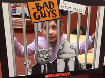 Child holding bad guys photo booth prop