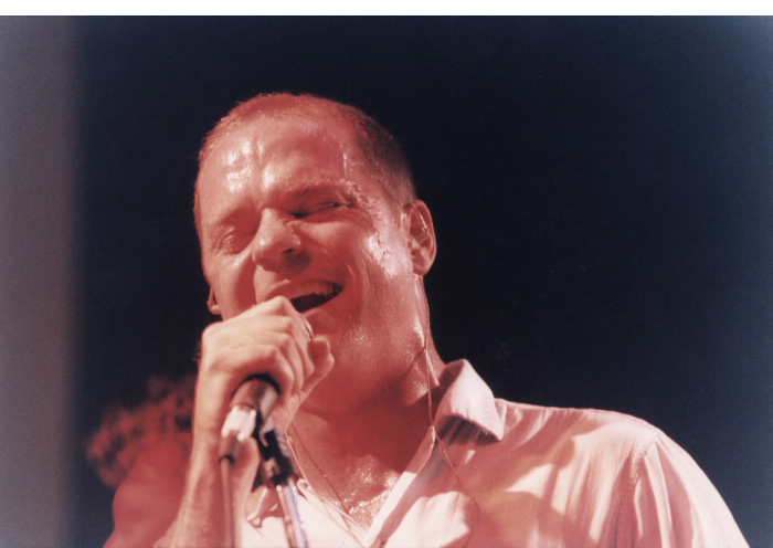 A man exerting himself signing into a microphone
