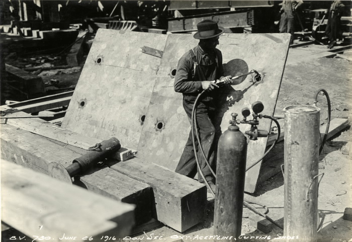 Man in overalls with tool hooke up to canister cutting holes in metal