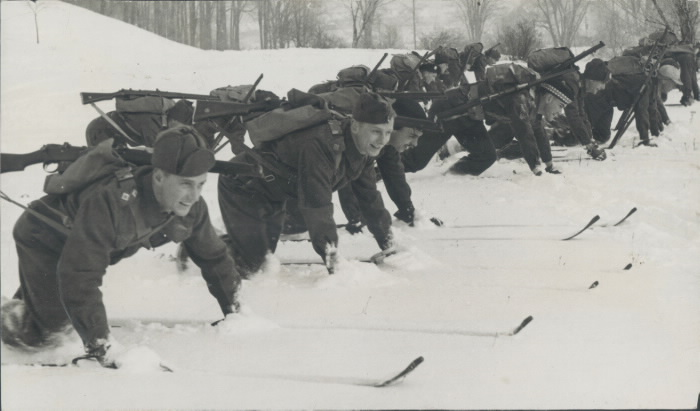 A large number of men on skis kneeling on the snow smiling in uniforms