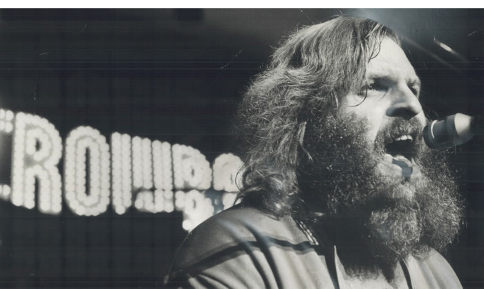 Bearded man signing in microphone