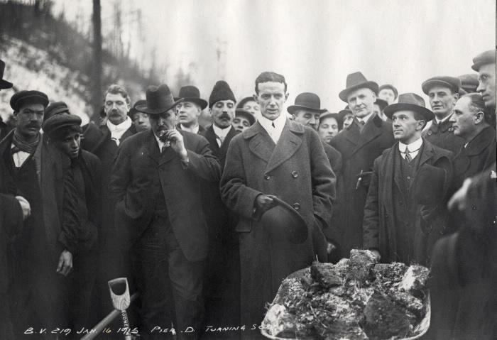 Men in formal attirecircled around a men with wheelbarrow full of dirt