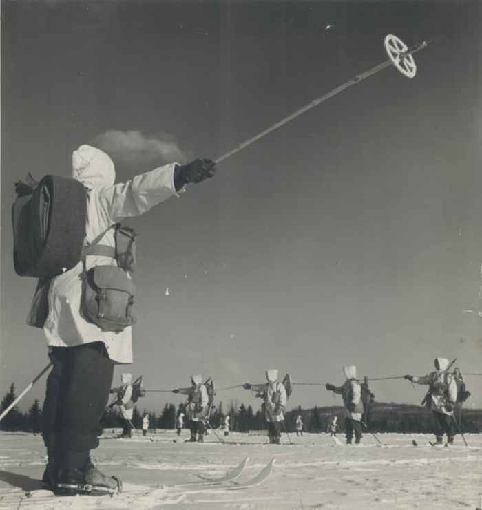 Men in white uniforms on skis holding up ski poles