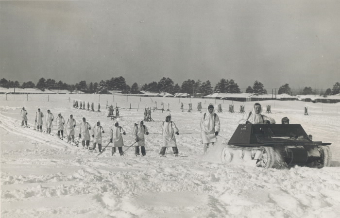 A line of men on skis are pulled by a rope hooked to a small tank