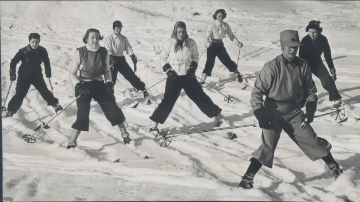 Women in ski gear proceed down a smill hill behind an instructor