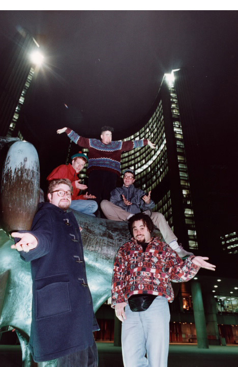Five young men posing on statue in front of Toronto City Hall at night
