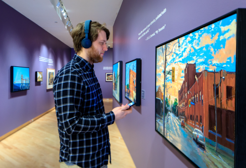 Man wearing headphones and holding phone looking at painting in the TD Gallery