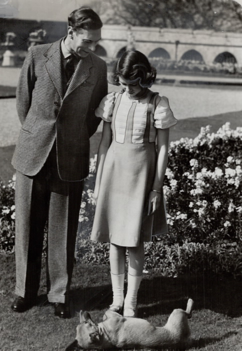 Man and young girl looking down at a dog on his side