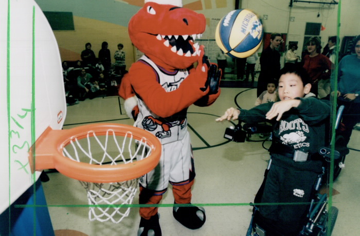 Boy in wheelchair shots a basketball as the raptors mascot claps