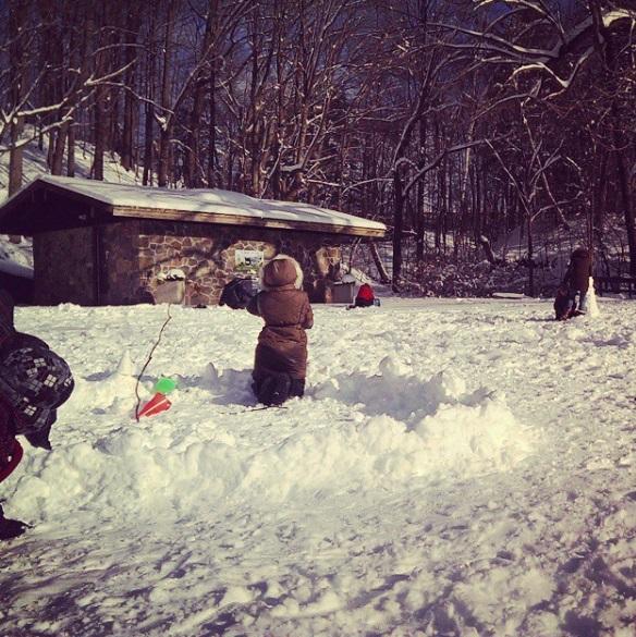 Children building snow shelters