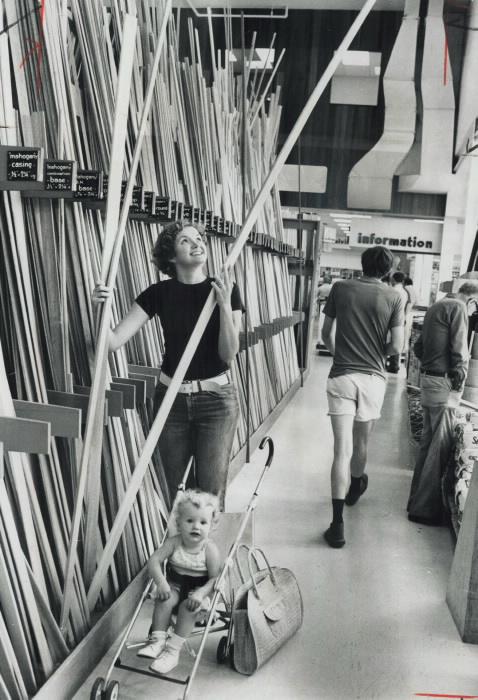 1976 vintage photo Mrs. Debi Cushing; with daughter Dana buying some lumber at Lansing Buildall's store