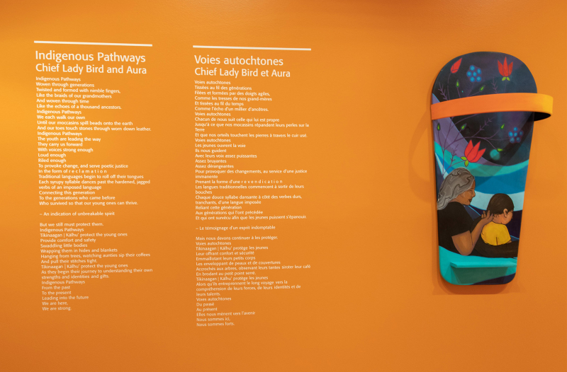 Orange wall with painted board on one side and on the other side an English poem and its french translation  the English one titled Indigenous Pathways by Chief Lady Bird and Aura