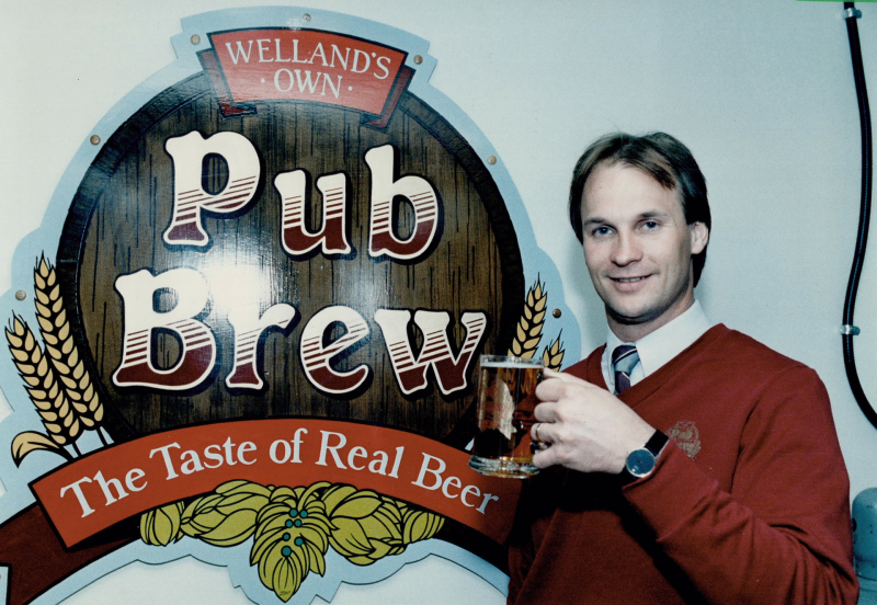 Moe Coutu, general manager of the Atlas Hotel in Welland, raises a glass in a toast to the emblem of his pub's made-in-the-house brew in 1986