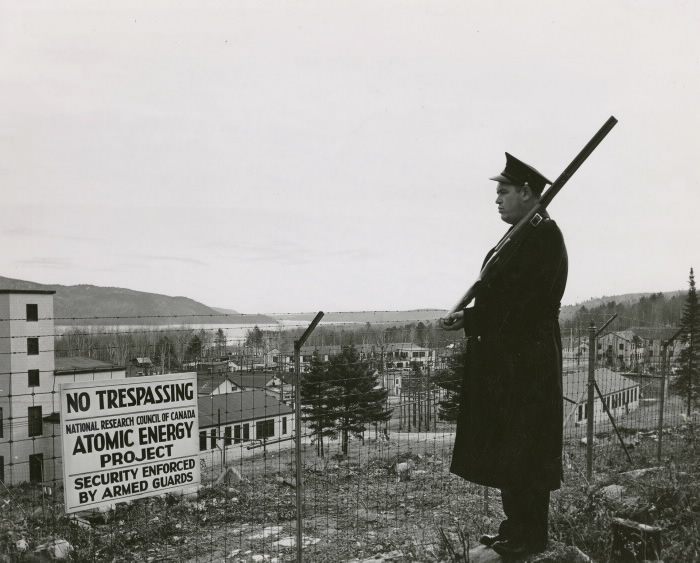 A guard stands watch at the perimeter of the science base. He holds a musket ceremoniously and looks towards the buildings.