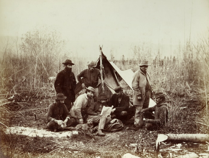 Men and dog resting at a temporary camping location with tent in the outdoors