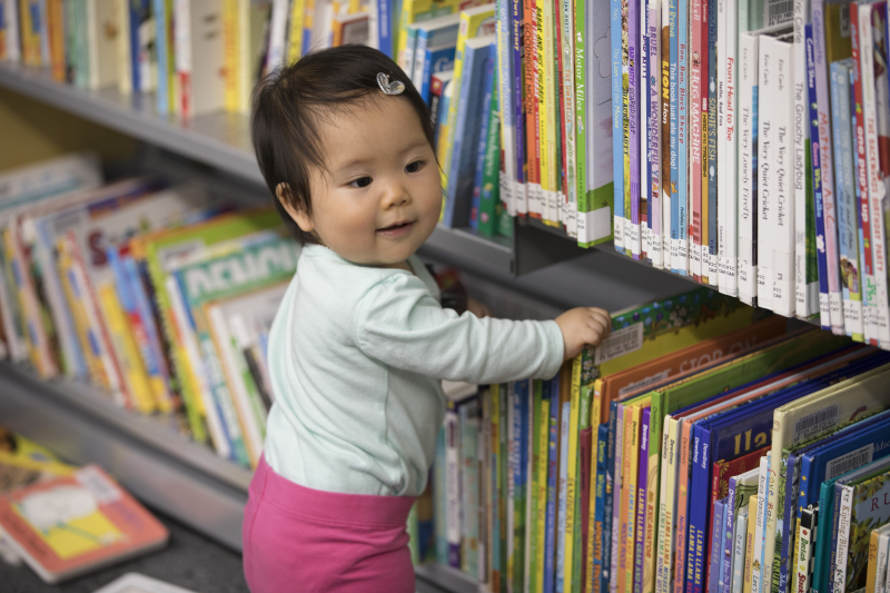 Toddler choosing books at a bookshelf