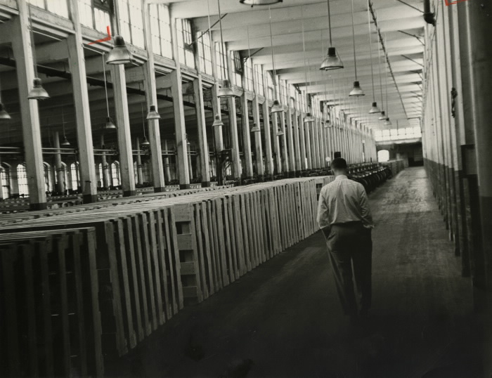 Empty factory with man walking down hallway