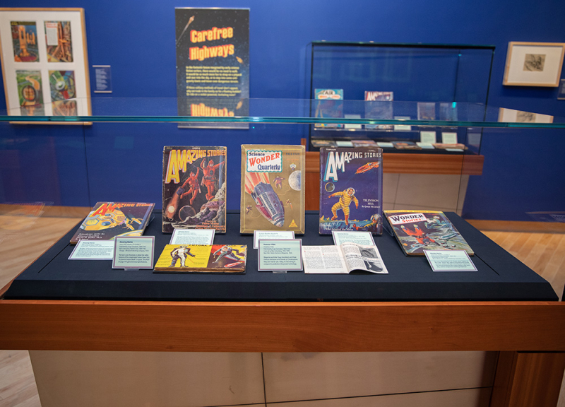 Museum glass display case with books and science fiction items inside
