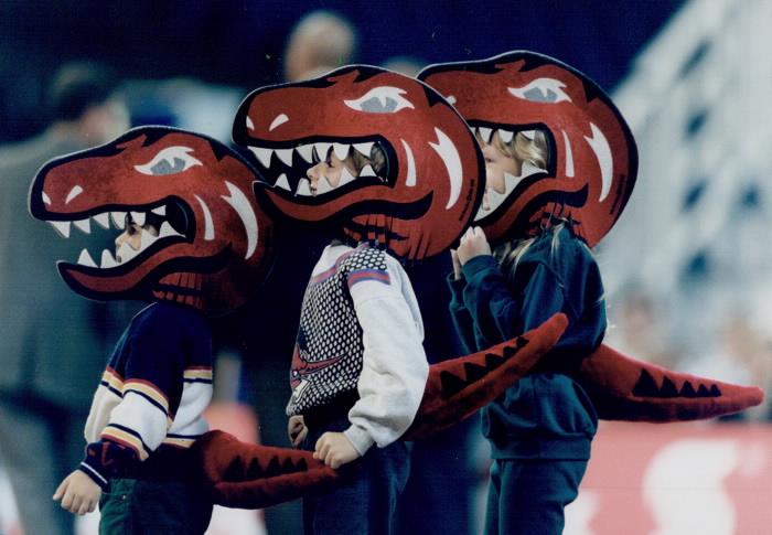 Kids with Raptors mascot head masks watching game