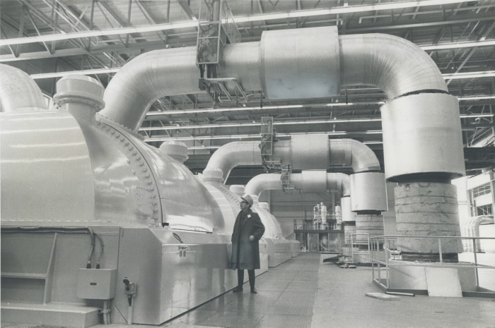 Man in construction hat stands underneath a large pipe in a factory