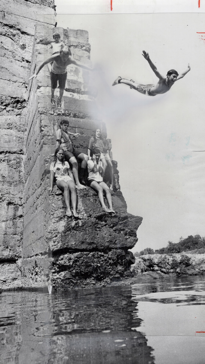 Flying from the heat. Three boys dive together from the 25-foot-high Erindale Dam for a cooling dip in the water in the Credit River, 1971