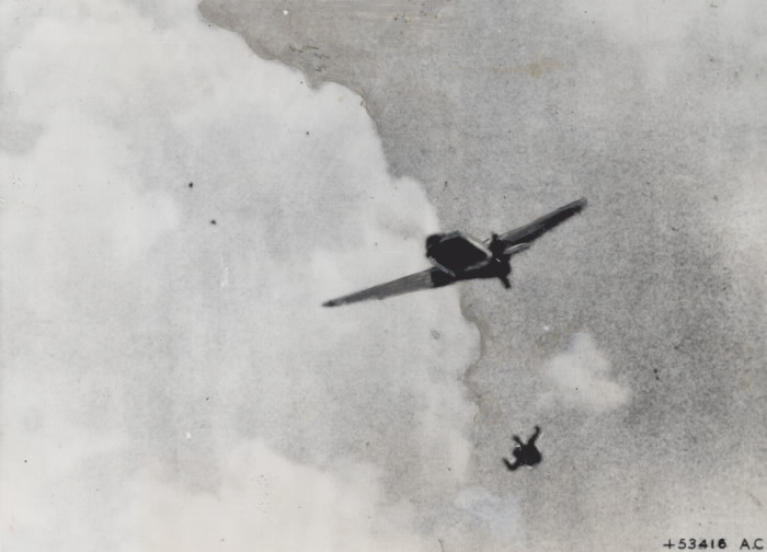 A German fighter pilot ejects himself from his plane while under fire from Allied forces.