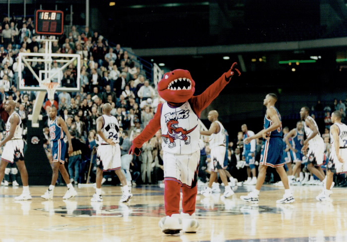 Raptors mascot with team behind it pointing out to crowd