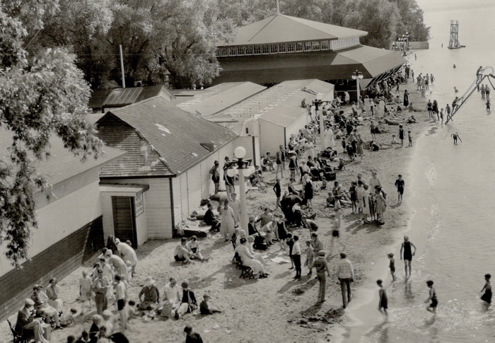 Beach with children in water and adults on beach by building in vintage clothes