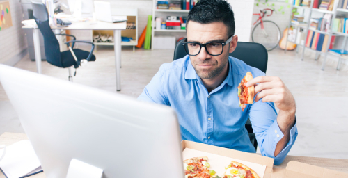 A man eating pizza in front of a computer station.