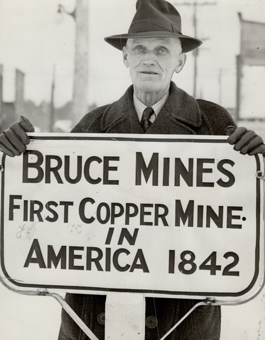 "Photo of Albert Grigg, mayor of Bruce Mines in 1943, holding sign that reads ""Bruce Mines: First Copper Mine in America 1842""."