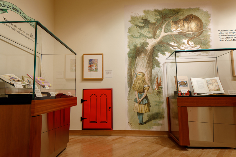 Gallery interior with cases with books and on the wall is an Alice in Wonderland mural as well as a swinging red door