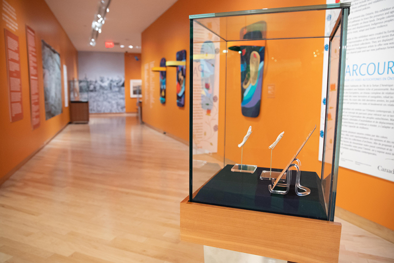 Interior of gallery with case in focus with objects inside and beyond colourful artwork