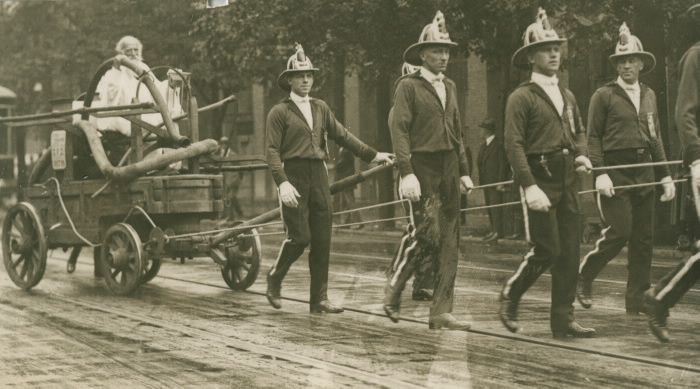 1923 photo of Toronto Labour Day Parade of firemen pulling Toronto's original fire wagon