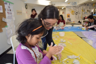 Artist Mariana and a child working on a clay sculpture.