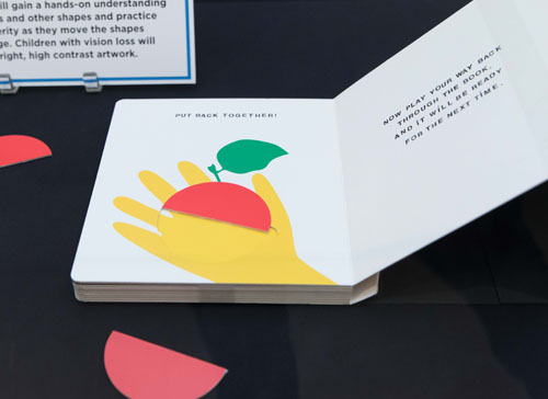 Exhibit case with open board book with illustrated hand and half a fruit with e other half of fruit as a piece out of the book