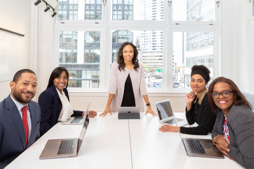 A group of diverse people in a meeting with a woman standing in the middle.